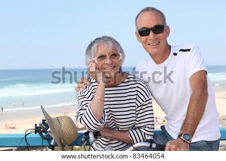 Senior couple riding bikes by the beach - stock photo