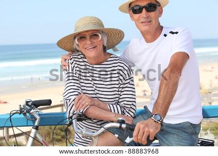 Senior couple riding bikes by the ocean - stock photo
