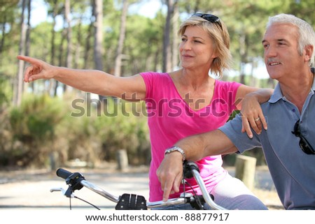 senior couple riding bikes in the park - stock photo
