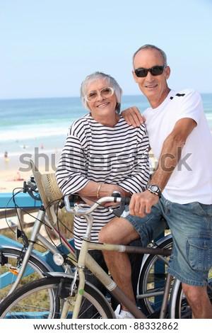 senior couple riding bikes on the beach - stock photo