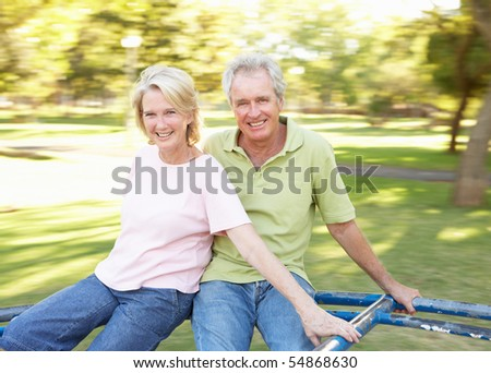 Senior Couple Riding On Roundabout In Park - stock photo