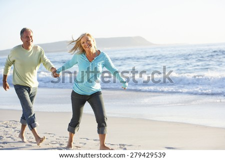Senior Couple Running Along Beach - stock photo