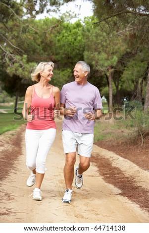 Senior couple running in park - stock photo