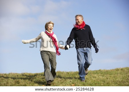Senior Couple Running In The Park - stock photo