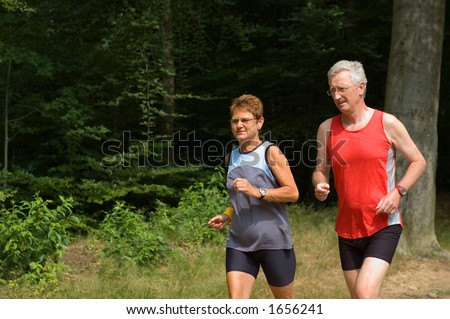 senior couple running in the woods - stock photo