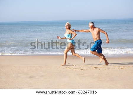 Senior couple running on beach