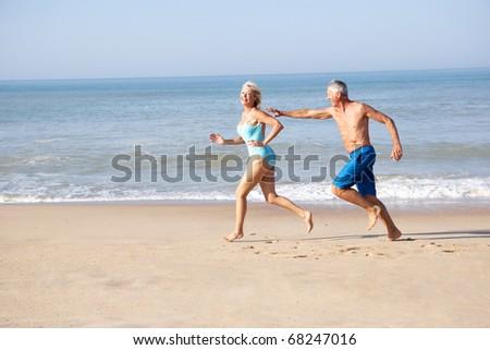 Senior couple running on beach - stock photo