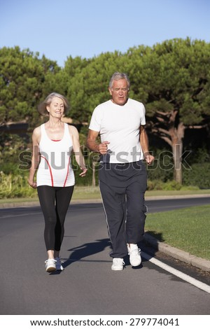 Senior Couple Running On Road