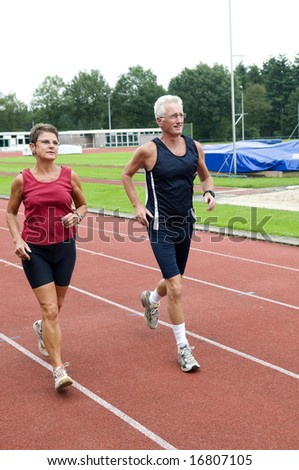 Senior couple running together on a track in a stadium. - stock photo
