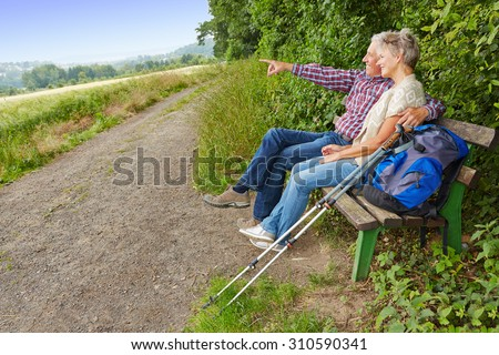 Senior couple searching goal in the distance while sitting on a bench - stock photo