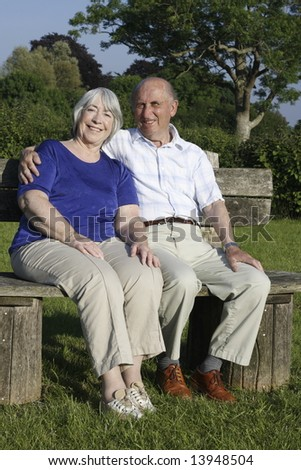 Senior couple seated in a park on a summers evening. - stock photo