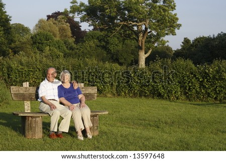 Senior couple seated on a park bench on a summers evening. - stock photo