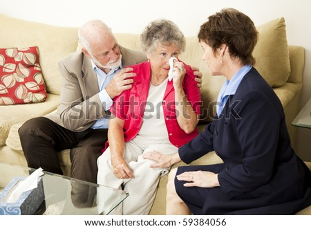 Senior couple sees a therapist to cope with grief.  Could also be funeral director meeting with clients. - stock photo
