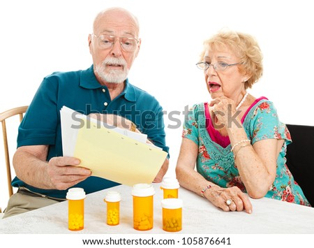 Senior couple shocked by the high cost of their medical bills.  White background. - stock photo