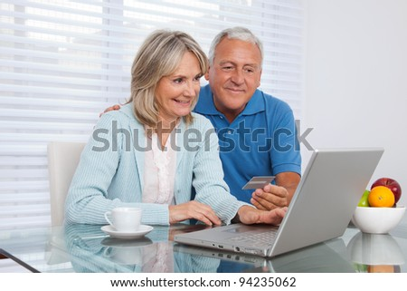 Senior couple shopping online using laptop with credit card - stock photo
