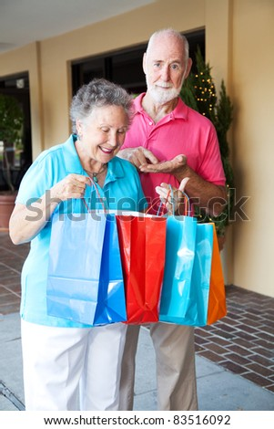 Senior couple shopping. She's happy with her purchases, and he's upset because she spent all his money. - stock photo