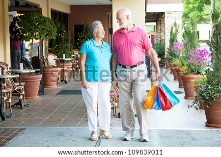 Senior couple shopping together at an outdoor mall, holding hands.