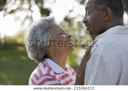 Senior couple showing affection in park, woman stroking man's chest, smiling, face to face, profile, close-up