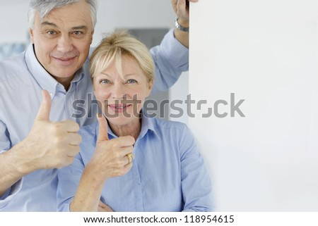 Senior couple showing thumbs up - stock photo