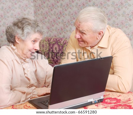 senior couple sit ar the laptop and discuss - stock photo