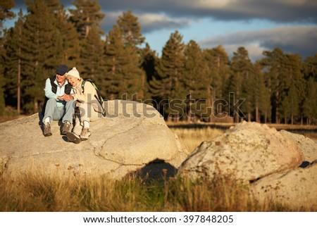 Senior couple sit on a rock near a forest, California, USA - stock photo