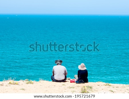Senior couple  sitting against each other, watching the beautiful sew - stock photo
