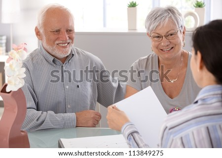 Senior couple sitting at desk at financial advisor, smiling.