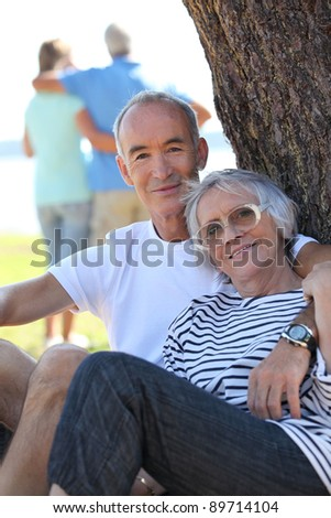 Senior couple  sitting by a tree in the summertime