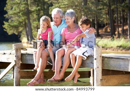 Senior couple sitting by lake with grandchildren - stock photo