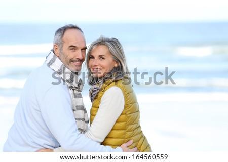 Senior couple sitting by the beach  - stock photo