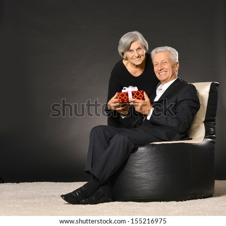 Senior couple sitting in armchair and celebrating holiday with gift - stock photo