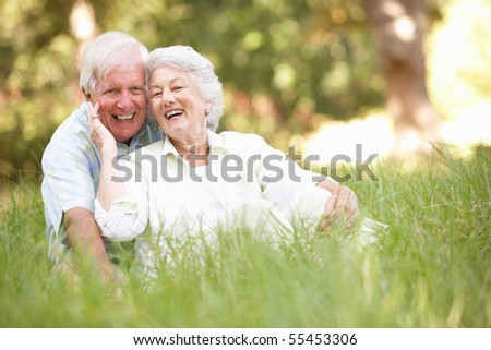 Senior Couple Sitting In Park - stock photo