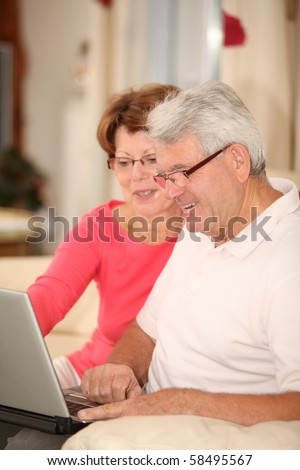 Senior couple sitting in sofa with laptop computer - stock photo