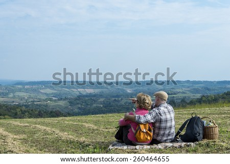 Senior couple sitting in the field - stock photo