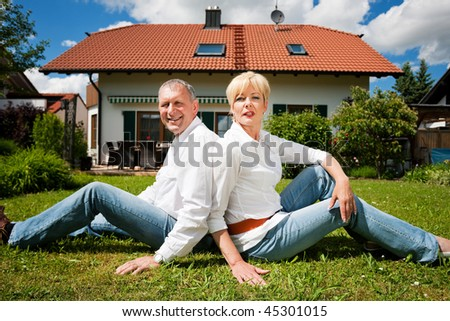 Senior couple sitting in the sun on the lawn in front of their new home - a detached house