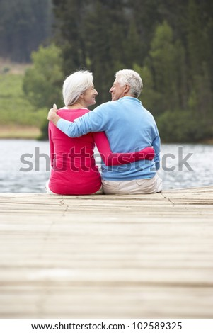 Senior couple sitting on a jetty - stock photo