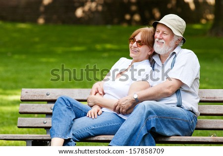 Senior couple sitting on a park bench hugged, shallow depth of field - stock photo