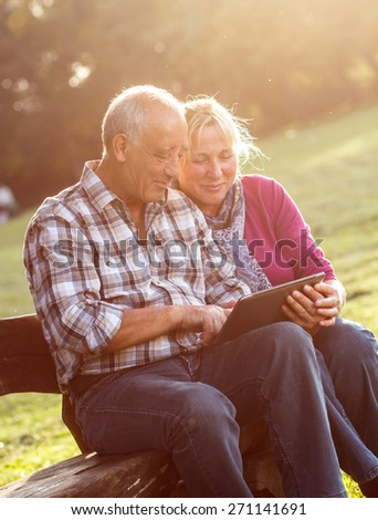 Senior couple sitting on a park bench on sunny autumn day with tablet and relaxing.  - stock photo