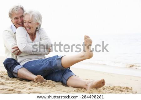 Senior Couple Sitting On Beach Together - stock photo