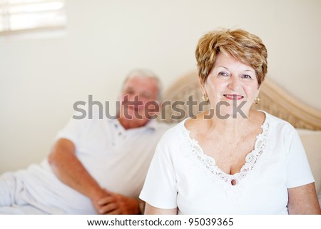 senior couple sitting on bed - stock photo