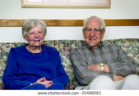 senior couple sitting on couch - stock photo