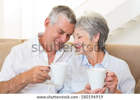 Senior couple sitting on couch drinking coffee touching heads at home in living room - stock photo