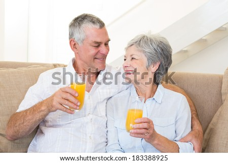 Senior couple sitting on couch drinking orange juice at home in living room
