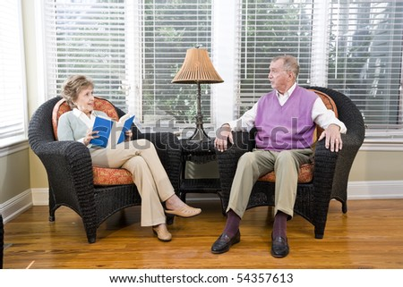 Senior couple sitting on living room chair reading and chatting - stock photo