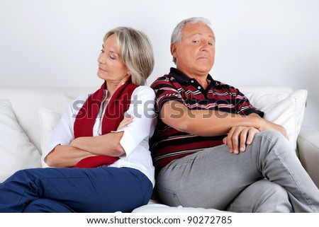 Senior couple sitting on sofa after argument - stock photo