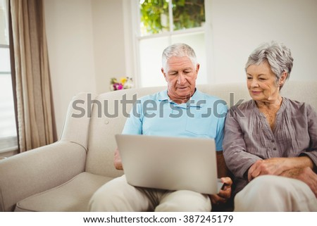Senior couple sitting on sofa and looking at laptop in living room - stock photo