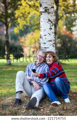 Senior couple sitting together and making selfie with cellphone in park - stock photo