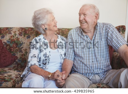 Senior couple sitting together hand in hand on the sofa. happy mature couple looking relaxed and content together. - stock photo