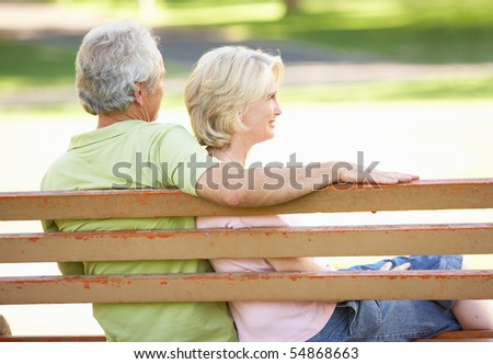 Senior Couple Sitting Together On Park Bench - stock photo