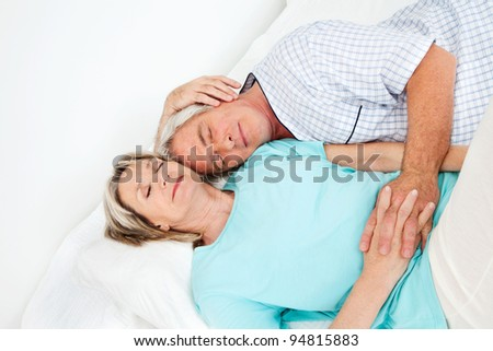 Senior couple sleeping relaxed together in bed - stock photo